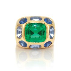 Gold, Emerald and Multicolored Sapphire Ring, Chanel 18 kt., the polished gold bombe ring centering one gypsy-set cushion-shaped emerald approximately 5.85 cts., surrounded by 8 gypsy-set cushion-shaped cabochon sapphires and purple sapphires