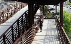 A woman jogs up a ramp toward a pedestrian overpass in San Luis Obispo, Calif.