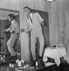 Sammy Davis Jr. tap dances on a table in his hotel room on May 3, 1966.