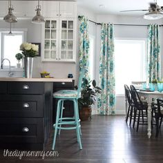 """I painted some old counter stools we had with chalk paint, and reupholstered the seats with fabric that matched the drapes. The flooring is an inexpensive laminate from Lowe's (Allen + Roth Provence Oak) that we installed throughout the house before the cupboard installation.""   - CountryLiving.com"