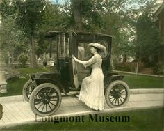 """Very early electric car. According to the catalog card, handwritten note on back of photo"""" """"property of Inez Lyon who had her first auto ride with Mrs. Callahan in front of Callahan house. Amy Herron & Mrs. Lyon & Mrs. Callahan rode in a parade down town. (about 1901)"""". However, the print has been mounted on 8 1/2"""" x 14"""" matboard, obscuring any writing on the back.  Awesome early photo from Longmont"""