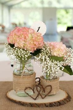 Love the design! Baby's breath and pink flowers, in mason jars wrapped with burlap on a thinly sliced piece of wood!