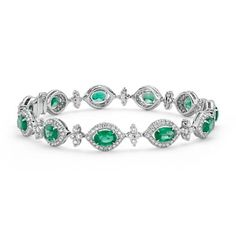 This dramatic gemstone bracelet showcases vibrant emeralds highlighted by a dazzling halo of pavé-set diamonds.