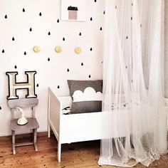 Small black raindrop wall decals placed in a pattern in place of wallpaper on a white wall in a nursery. The crib s white and has a brown pillow on top.