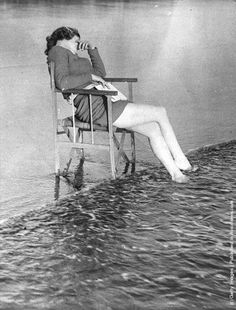 The tide comes in on a woman at Barry Sands who has fallen asleep in the sunshine. (Photo by Fox Photos-Getty Images). 10th June 1938