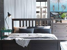 HEMNES grey-brown bed with RÅSKOG turquoise kitchen trolley and BJÖRNLOKA RAND white/black/orange cushion cover