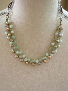 Bohemian meets country chic with this fabulous leather multi-strand necklace! 3 strands of 6mm amazonite stones, glowing champagne freshwater pearls and sparkling 6mm pale aqua czech glass beads are clasped by 2 clear faceted glass rondells and suspended from distressed brown leather cords.    Each leather loop is neatly reinforced with wraps of non-tarnish artistic wire.    This necklace is approximately 19 and topped with our choice of a pretty whitewashed button. The strands are…