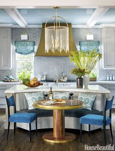 "A Lewis chandelier and Leyden sconces from Hudson Valley Lighting brighten the Atlanta kitchen. The banquette — covered in Interlude from Thibaut's Portico collection of Sunbrella fabrics — offers cozy seating around a Grothouse walnut table with metallized banding. Machine-washable linen shades by Thibaut are ""kitchen-practical,"" says Quinn."