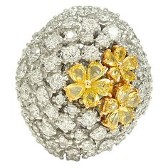 Delightful Diamond Flower Ring. A dramatic 18k white gold ring featuring three flowers made of pear shaped fancy yellow diamonds surrounded with an array of white diamonds. Contemporary