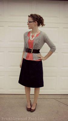 black skirt, short, coral pink, pearls, heels, belt, grey cardi