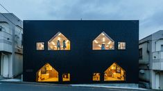 Hibinosekkei has completed a nursery in Yokohama, which features plywood-lined interiors and house-shaped openings set into its dark facades.