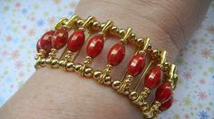 """This lovely stretch bracelet is designed with Czech paprika-colored faceted glass luster """"footballs"""" speckled with copper and 1-inch gilt quilter's"""