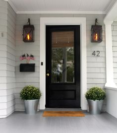 glossy black front door, flanked with simple sleek planters