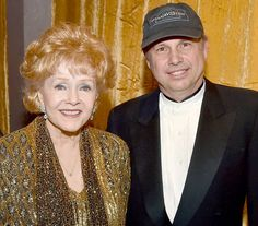 Debbie Reynolds and Todd Fisher pose in the trophy room at TNT's 21st Annual Screen Actors Guild Awards at the Shrine Auditorium on Jan. 25, 2015, in Los Angeles.