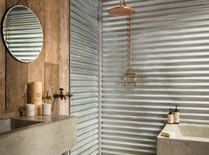 Copper shower head, galvanised corrugated iron replaces conventional tiles in this rustic bathroom