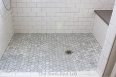 The shower floor is hexagon-shaped marble tiles with darker gray grout. We had the marble sealed and upgraded all the grout to one that resists mold and fading.