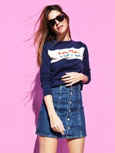 Blogger Gala Gonzalez wears a Bella Freud knit sweater, button-down denim mini skirt, and round sunglasses