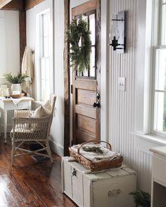 Beautiful farmhouse living - hefty wood door, white decor, mill work, beadboard = simple living