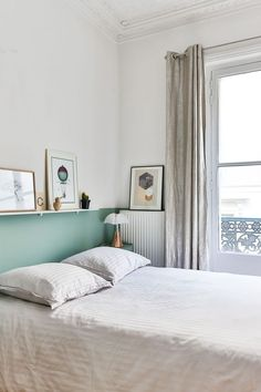 Une tête de lit vert d'eau égaye cette chambre toute blanche