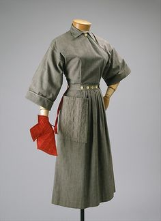 """This is a """"pop-over"""" dress created by American designer Claire McCardell. It features many of McCardell's typical design features, including decorative buttons and a large pocket. This dress is made of cotton and is from the year 1942."""