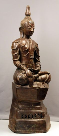 Bronze Sitting Buddha Period: 1700 Country: Burma-Laos Border Height: 115cm Sitting n bhumisparsamudra on a double lotus, downcast expression and marvellous brownish patina. The veil has a serpent finial near of the heart, symbol of wisdom. Perfect condition and untouched Buddha. VERY RARE.