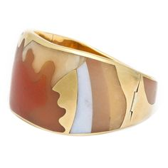 A rare and spectacular 1970s Tiffany bracelet of 18K yellow gold inlaid with various colors of carved agates, fit seamlessly together like puzzle pieces, forming an abstract design of a woman against a sunrise. Marked: T & Co., C, and 18K. 82.7 grams. 1 3/16 widest point x 6 1/2 inch interior.