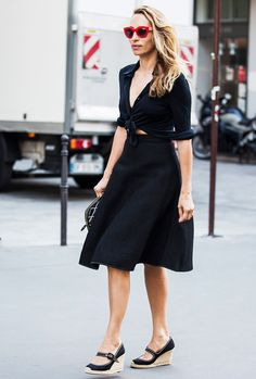 A black button-down shirt is tied in front and worn with a black a-line skirt, espadrilles, clutch, and red sunglasses