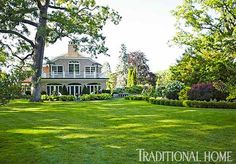 An expansive lawn and manicured gardens make this yard memorable - Traditional Home® / Photo: Peter Krumhardt / Garden design: Liz & Peggy Olsen