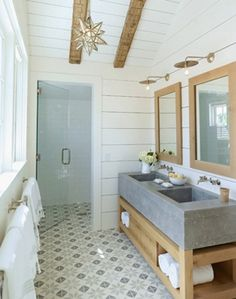 bathroom with groove walls & ceiling, rustic exposed wood beams, moravian star pendant, wood double bathroom vanity with concrete sinks & countertop, wood mirrors and wall-mount faucets.