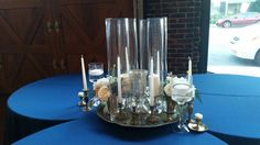 A unique spin on the gift table. Cloverleaf table design with a vintage brass tray, vintage brass candlesticks, and tall cylinder vases with taper candles.