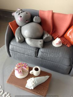 A birthday cake for a lady that loves hippo's and cake! A hippo on the sofa, enjoying tea and cake.
