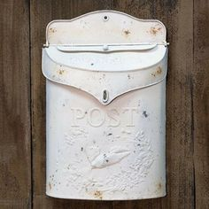 "White Post Box - Our White Post Box is made from metal with a distressed, white painted finish. The mailbox is embossed with scrollwork, a bird in flight, and the word ""Post."" It includes a slot for mail as well as a hinged top that opens to store larger items. Includes a pre-drilled hole for hanging. This rustic mailbox will make a charming addition to your home."
