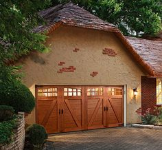 Composite roll-up garage doors have all the energy efficiency of a modern, insulated garage door but use a frame-and-panel design made from stained, maintenance-free materials and cost only 10 percent more than a cedar door. Shown: The hardware, arched windows, and bracing of the Canyon Ridge Ultra-Grain steel and composite carriage-house door would be right at home on a Victorian-era garage. Starting at $2,200 for a single-car door, uninstalled; Clopay Cedar Garage Door, Garage Door Hardware, Garage Door Styles, Garage Door Design, Halle, Carriage Doors, Carriage House, Sectional Garage Doors, Cheap Doors