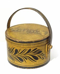 "This finely made bentwood box with wooden handle retains the original yellow painted finish highlighted with black foliate and striped decoration and initialed on the top ""J.H. Wigg"". Dimensions: H 4 ¾"", Diameter 7 ¼""  Date / Circa: c.1840  Maker / Origin: American"