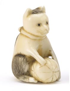 Meiji/Taisho period, (circa 1900) A marine ivory figure of a seated cat with a black spotted coat and playing with a ball, signed Meigyokusai