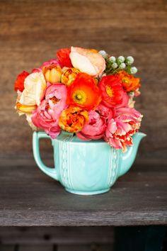 Beautiful orange & coral flowers in a mint-teal teapot. Get a similar-looking custard jug here: http://shop.kamersvol.com