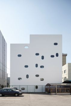 Striking white walls with oblong windows enclose a minimal five-storey office in the capital of Japan's Aichi Prefecture, by Yoshihiro Kato Atelier.