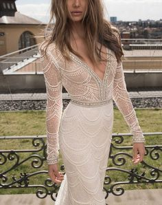 Masterwork beading, embroidery and sequins shimmer throughout the sheer décolleté bodice and figure-accentuating mermaid skirt of this alluring wedding gown.