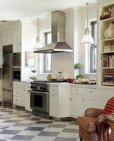 subway tile backsplash, the oven between the 2 windows, and vertical bookshelf for cookbooks