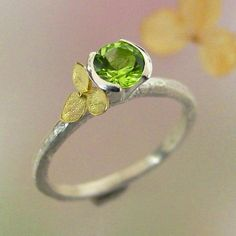 A beautiful bright green 5 mm peridot is set into a split bezel on one of my textured stacking rings. Next to the stone sits a single hydrangea blossom cast in solid 18k gold. The perfect little hydrangea measures just 6mm and it sits on a 1.9mm wide sterling band that is detailed with some tool marks and textures that give it a slightly primitive feel. The ring has a soft, satin, burnished finish.  This ring can be stacked with most of my other rings, the last photo shows it stacked with my…