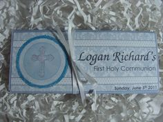 To Shop this Candy Bar: www.etsy.com/shop/CandyBarBoutique     This religious sky blue cross candy bar is the perfect favor for a special boy's First Holy Communion. We can also convert this candy bar into one for a New Baby Boy, Christening, Dedication, or other Religious Event. The circle around the Cross has light blue glitter and the cross itself has white glitter. Adorned with a white bow, this candy bar favor makes a special presentation at your next religious event!