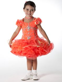 This short pageant dress by Unique Fashion Pageant Gown UF1056 displays spaghetti straps, gorgeous beaded bodice, bows and flowers accent the sleeves, and a full short layered skirt with alternating colors completes this look. Two pieces set. This adorable dress is a great selection for your next pageant.