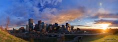 A panoramic view of the downtown Calgary skyline at sunset.