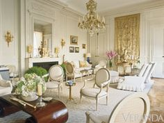 Henri Samuel and Susan Gutfreund - Simple white slipcovers, a wonderfully worn dhurrie, and creamy millwork give a grand Parisian salon filled with fine antiques a sublime, accessible grace.