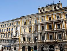 Photo made in two great and historic palaces of Trieste in Friuli Venezia Giulia (Italy). In the image you see in the foreground the rich facade of columns of an important building located in the railway station square. To the left of the first building we see each other, free of columns but linear and full of windows, which has the same height as the roof and both the blue sky above.