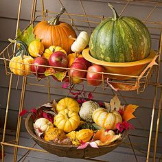 Tiered Fall Display - using a wire-tiered plant stand on your porch saves display space and creates an easy home for smaller items. Fill with a variety of fall decorations, such as pumpkins, gourds, foliage, and fruit, using wooden bowls and vintage crocks to add interest.