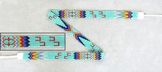 """Comanche Native American Beadwork Hat Bands    A one of a kind green turquoise/multi rainbow and horseshoe cut bead hat band was made by nationally recognized Comanche artist Jr. Weryackwe. The hat band measures 5/8"""" high x 22-1/4"""" long. It's finished with white leather ends and ties each 8"""" long. Signed by the artist.  $175.25"""