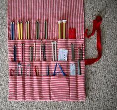 Knitting Needle Roll Up Case, Knitting Needle Organizer Case, 24 Pockets: 3 Rows of 8 in assorted sizes and widths.  Fold-down flap covers contents.  Permanently attached tie. Overall measurements - lying flat and open: approx. 28.5 x 14.  Accommodates ALL size and types of needles and accessories: double points, circulars, long and short straight needles.  Keep all your necessities handy and convenient.    Washable. All cotton - Red White stripe cotton.    Also perfect for artist brushes…