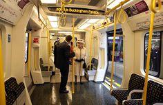 Queen Elizabeth II stands onboard a tube
