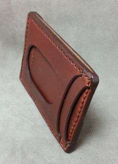 Hand cut and stitched leather minimalist wallet. A minimalist wallet made with quality vegetable tanned leather that features 2 pockets for I.D. and cards etc.. a unique cash strap/card holder on t...
